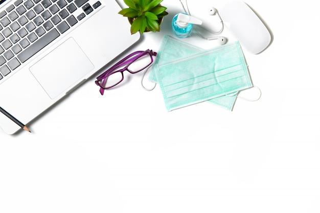 Maska chirurgiczna i butelka dezynfekująca lub żel alkoholowy z laptopem na białym tle