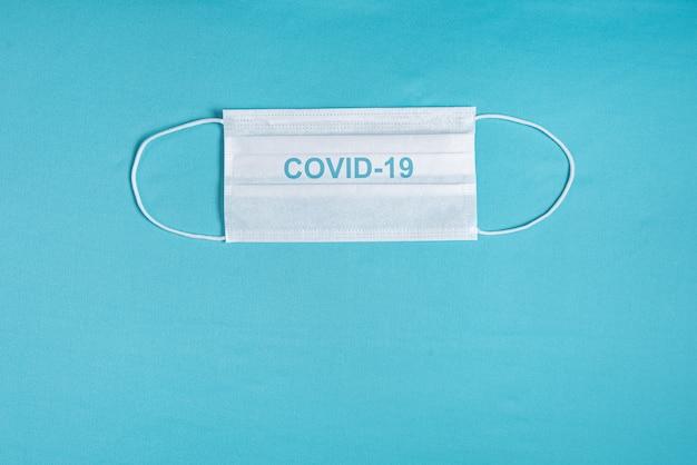 Maska chirurgiczna na minimalistycznym niebieskim tle