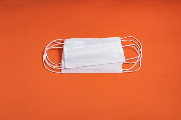 Maska chirurgiczna na minimalistycznym pomarańczowym tle