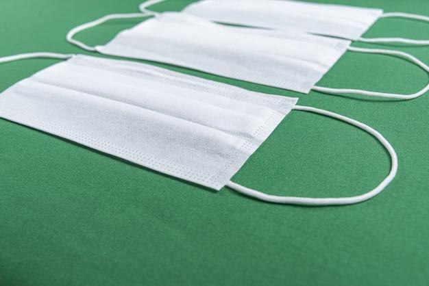 Maska chirurgiczna na minimalistycznym zielonym tle