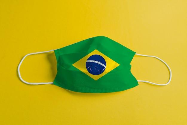 Maska chirurgiczna na żółtym tle z brazylijską flagą
