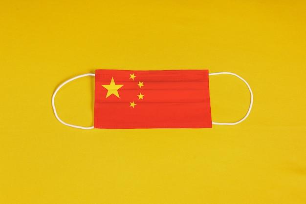 Maska chirurgiczna na żółtym tle z flagą chin