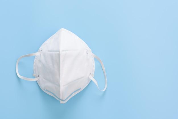 Maska chirurgiczna ochrona przed zarazkami przed wirusem koronowym na niebieskiej ścianie, płasko ułożona