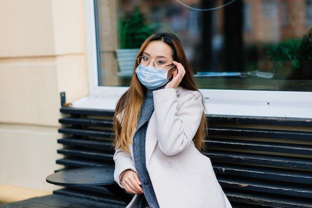 Maska chroniąca przed rozprzestrzenianiem się wirusa grypy chroniąca przed wirusami i chorobami grypy. azjatycka kobieta nosi maskę chirurgiczną na twarzy w miejscach publicznych. opieka zdrowotna.