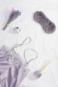 Maska do spania, jedwabna piżama, aromatyczny balsam, suche kwiaty lawendy na białej pościeli.