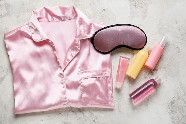 Maska do spania, piżama i kosmetyki na kolorowej powierzchni