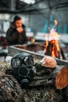 Maska gazowa przed ogniem, prześladowca je. postapokaliptyczny styl życia, dzień zagłady, horror wojny nuklearnej
