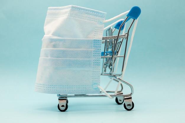 Maska i wózek na niebieskim tle, zakupy dla ochrony covid-19.