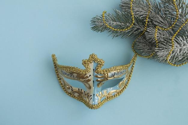 Maska karnawałowa i świąteczna kompozycja na niebieskim stole. widok z góry. skopiuj miejsce.