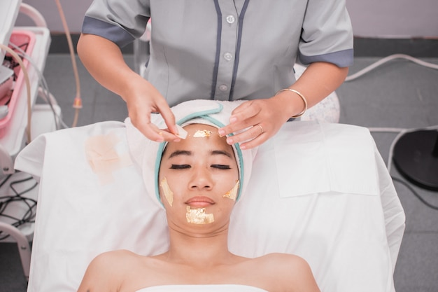 Maska kolagenowa. świecący zabieg na skórze przy użyciu złotej maski