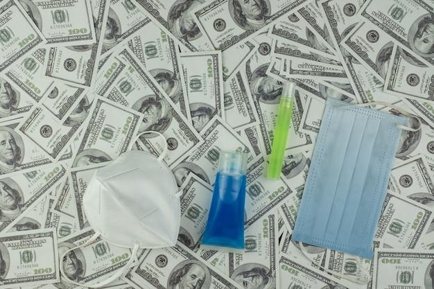 Maska lekarza i butelka z żelem alkoholowym chroniącym przed wirusami i pieniądze stos banknotów 100 usd