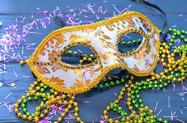 Maska mardi gras i koraliki na drewnianym stole. akcesoria karnawałowe madi gras, konfetti, maska świąteczna, wenecka lub karnawałowa. koncepcja celebracji maskarady.