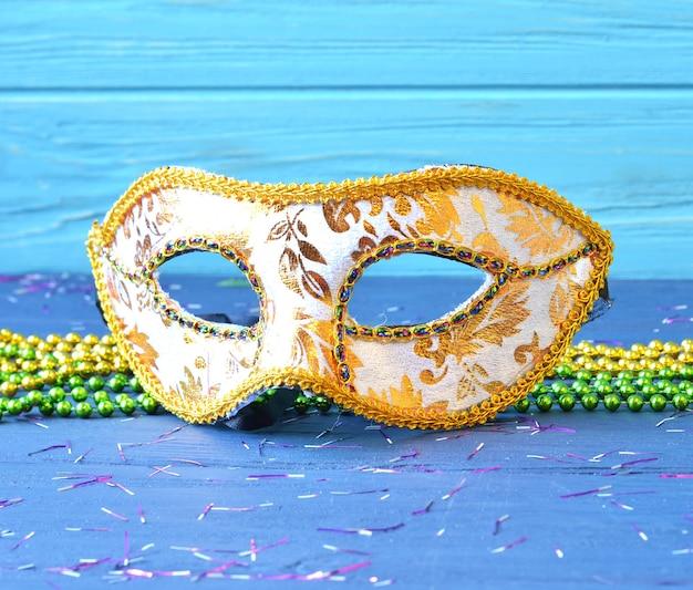 Maska mardi gras i koraliki na tle drewnianych. akcesoria karnawałowe madi gras