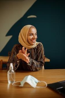 Maska medyczna i antyseptyczny, arabska dziewczyna w hidżabie w kawiarni uniwersyteckiej na tle. muzułmanka z książkami siedzi w bibliotece.