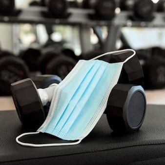 Maska medyczna i ciężarki na siłowni