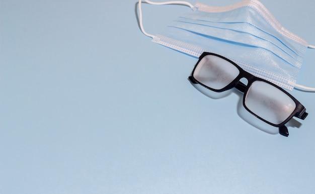 Maska medyczna i spocone okulary na niebieskim tle. pandemic covid 19.