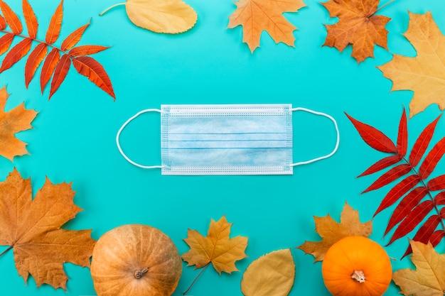 Maska medyczna między liśćmi klonu. jesienna kompozycja z maską, liśćmi klonu i dynią.