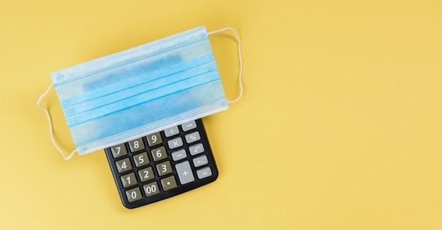 Maska medyczna na kalkulatorze z żółtym tłem. koncepcja obliczania kosztu masek. koncepcja sprzedaży maski.