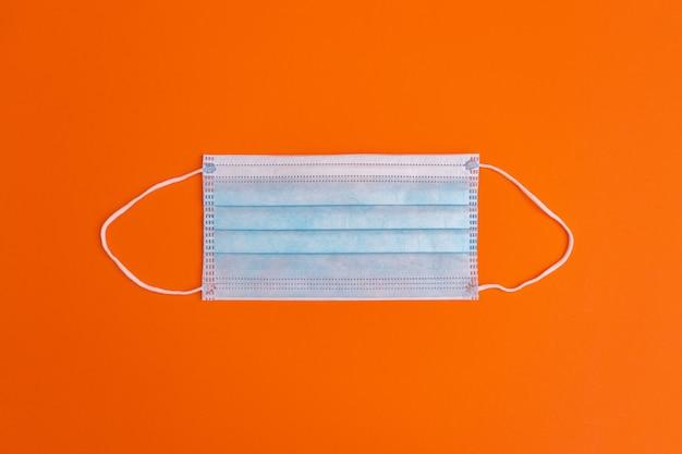 Maska medyczna na pomarańczowym tle.
