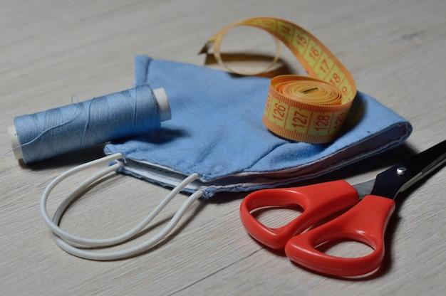 Maska medyczna ochronna w kolorze niebieskim, wykonana ręcznie z materiału tekstylnego. maska przeciwwirusowa, środki ochrony osobistej. koncepcja koronawirusa.