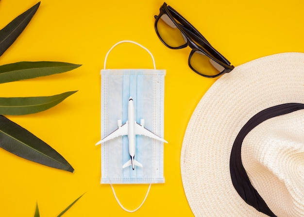 Maska medyczna, okulary przeciwsłoneczne, kapelusz, samolot, liście palmowe na żółtym tle. concept nie loty ani podróżować przez covid-19