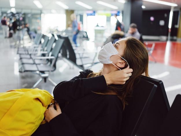 Maska medyczna pasażera na lotnisku czekająca na lot żółty plecak
