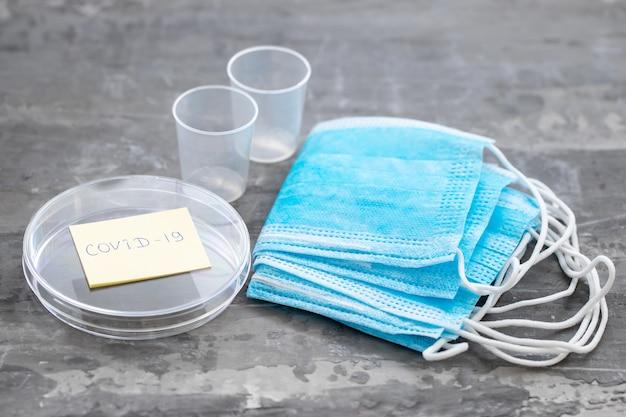 Maska medyczna, plastikowe kubki i inne przedmioty medyczne w powierzchni ceramicznej