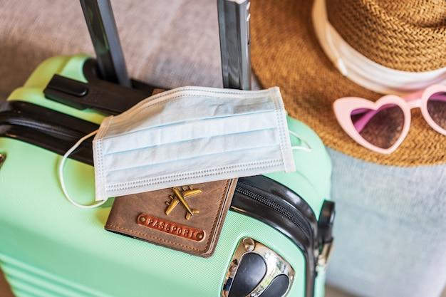 Maska medyczna z paszportem i bagażem przygotowuje na podróżowanie w nowym, normalnym stylu życia