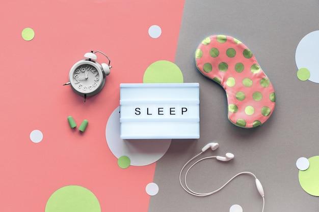 Maska na sen, budzik, słuchawki i zatyczki do uszu. środki uspokajające - pigułki, kapsułki i herbata.