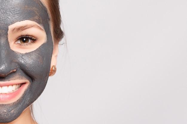 Maska na twarz kobiety. portret pięknej dziewczyny usuwanie czarnej maski kosmetycznej ze skóry twarzy. zbliżenie atrakcyjna młoda kobieta z naturalnego makijażu i maski skórki kosmetycznej na twarzy. wysoka rozdzielczość