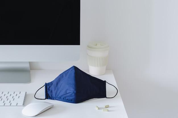 Maska na twarz nakładana na stół roboczy w biurze z lekarstwami chroniącymi przed rozprzestrzenianiem się wirusa.