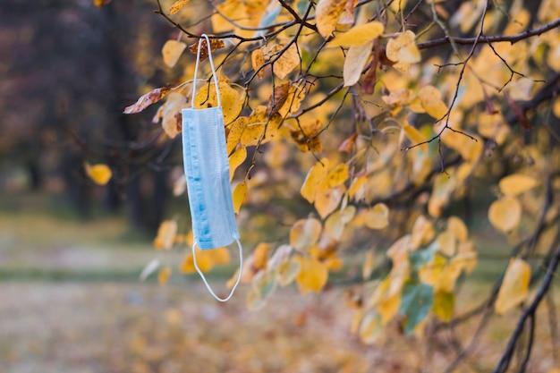 Maska na twarz wisząca na drzewie w jesiennym parku