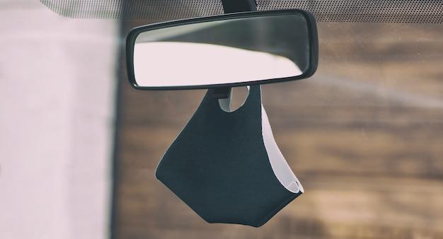 Maska na twarz zawieszona na lusterku wstecznym w samochodzie