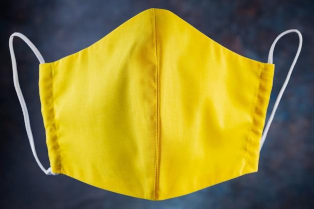 Maska ochronna na twarz. maska antywirusowa wielokrotnego użytku wykonana z żółtej bawełny. żółta maska ochronna