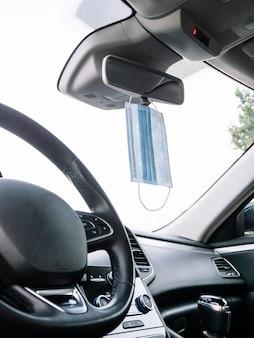 Maska ochronna na twarz zwisająca z lusterka wstecznego samochodu.