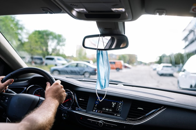 Maska ochronna na twarz zwisająca z lusterka wstecznego samochodu