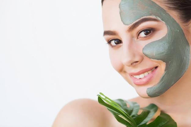 Maska. piękna uśmiechnięta kobieta stosuje maskę na twarzy