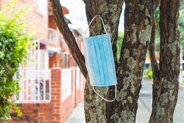 Maska porzucona na drzewie jako przykład zakończenia pandemii