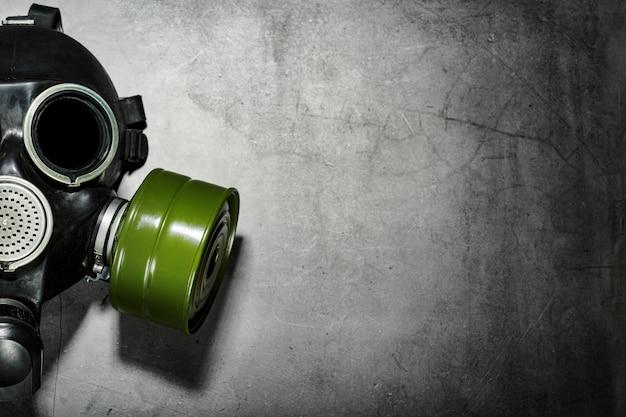 Maska przeciwgazowa na czarnym tle kamienia z zielonym wkładem filtracyjnym. koncepcja postapokaliptyczna.