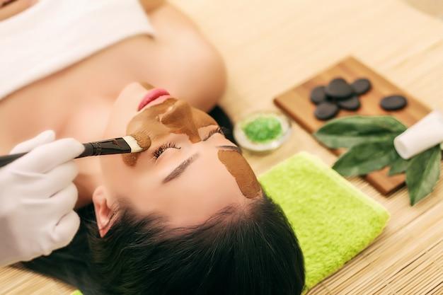 Maska spa kobieta w salonie spa. maska. maseczka z glinki do twarzy.