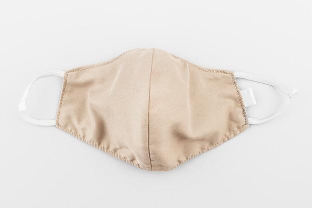 Maska z beżowej tkaniny na szarym tle