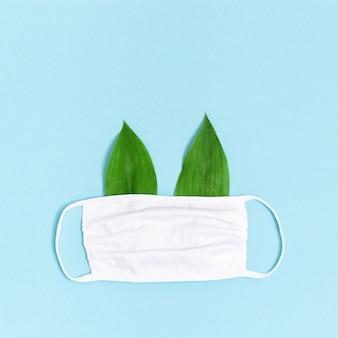 Maska z tkaniny medycznej z zielonymi liśćmi jak uszy. niebieskie tło z miejsca kopiowania.
