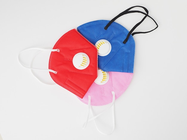 Maski antywirusowe w różnych kolorach na białym tle.