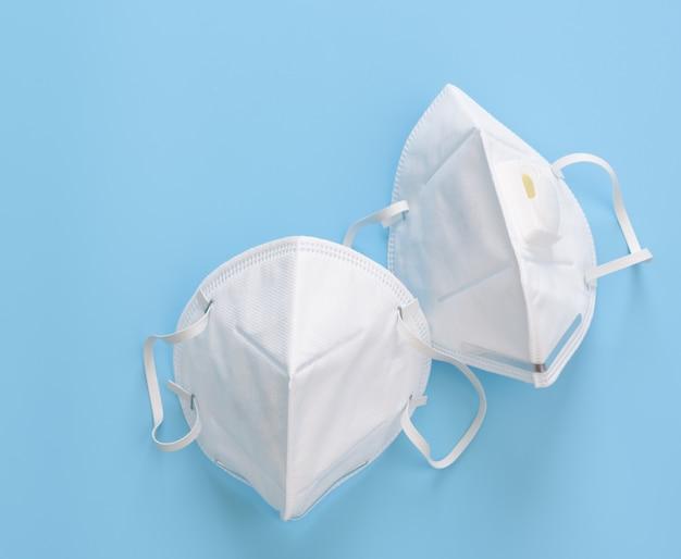 Maski chirurgiczne do noszenia ochrony przed zarazkami na niebieskiej ścianie, widok z góry