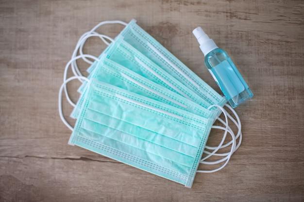 Maski chirurgiczne i butelka z żelem do dezynfekcji rąk
