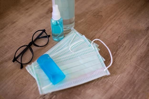 Maski chirurgiczne, okulary i butelka z żelem do dezynfekcji rąk