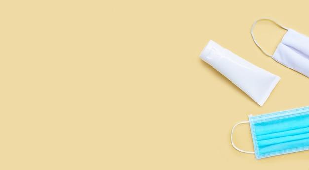 Maski i żel do dezynfekcji rąk żel w białej błyszczącej plastikowej tubce do ochrony higienicznego wirusa korony (covid-19). żółte tło