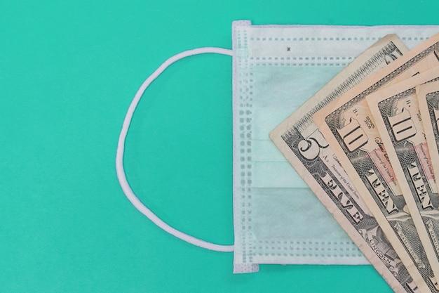 Maski medyczne i rachunki w dolarach jako symbol podwyższonych cen za ochronę dróg oddechowych przed wirusami. skopiuj miejsce