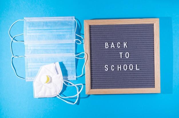 Maski medyczne i tekst z powrotem do szkoły