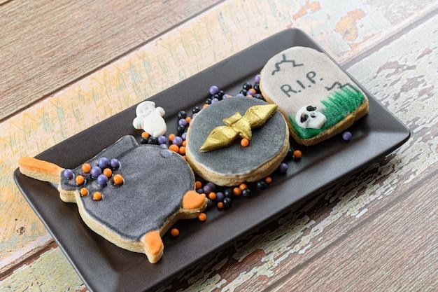 Maślane ciasteczka o tematyce halloween obok małych kulek cukru.